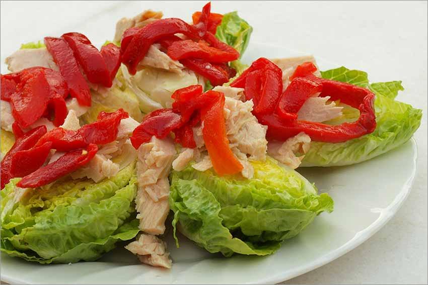 Ensalada de ventresca de atún con piquillos confitados, tartar de tomate y crujientes aros de cebolla frita.